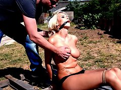 Tied up beauty is out in the sun dressed up in panties and heels, gagged and cold water is spilled all over her chest